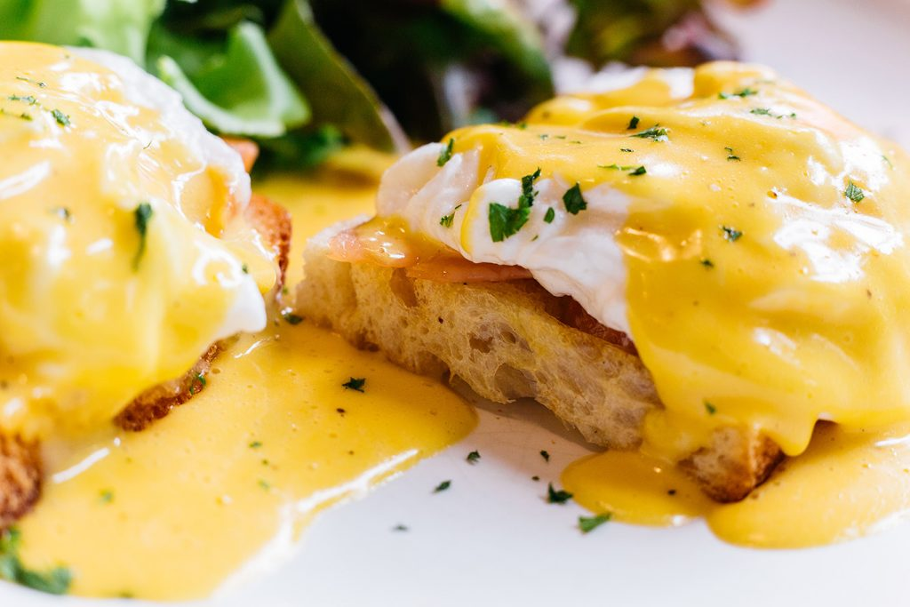 Close up Egg benedict served with salad in white plate on wooden table for delicious breakfast and brunch